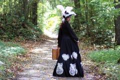 Девушка в ретро XVIII веке платья с valise в парке Стоковые Фотографии RF