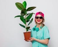 Девушка в розовой крышке и голубой футболке с зеленым растением стоковое изображение