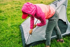 Девушка в розовой куртке с клобуком устанавливает шатер на зеленой траве Стоковое Фото