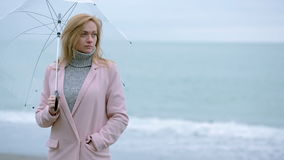 Девушка в розовом пальто с прозрачным зонтиком морем во время шторма видеоматериал