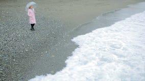 Девушка в розовом пальто с прозрачным зонтиком морем во время шторма акции видеоматериалы