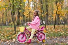 Девушка в розовом плаще и резиновые ботинки едет велосипед в t стоковое фото