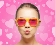 Девушка в розовых солнечных очках дуя поцелуй Стоковое Изображение