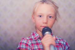 Девушка в рубашке шотландки держит микрофон в ее руках и смотрит в камеру стоковое фото rf