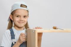Девушка в сборнике мебели прозодежд пробует затянуть винт Стоковые Фотографии RF