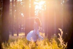 Девушка в светлом - голубое платье в солнце в середине леса стоковая фотография rf