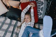 Девушка в свитере на кровати на зимний день Девушка имея потеху в доме Стоковое фото RF
