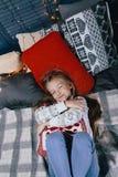 Девушка в свитере на кровати на зимний день Девушка имея потеху в доме Стоковое Изображение RF