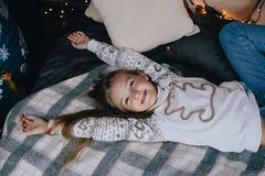 Девушка в свитере протягивая в кровати Девушка имея потеху в доме Стоковое Изображение RF