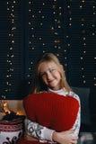 Девушка в свитере сидя на кровати и обнимая красную подушку Стоковая Фотография RF