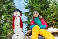 Девушка в связанной шляпе и шарфе играя с снеговиком Стоковое Фото