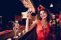 Девушка в сексуальном обмундировании демона представляя на баре с стеклом шампанского Стоковое Изображение