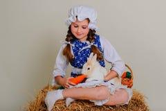 Девушка в сене подавая моркови зайчика пасхи Стоковые Изображения