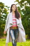 Девушка в сером пальто на зеленом glade Стоковое Фото