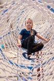 Девушка в сетчатом рукаве объекта парка атракционов взбираясь Стоковое фото RF