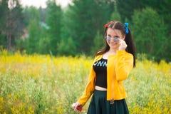 Девушка в синих стеклах и зеленой юбке на луге цветка стоковое фото