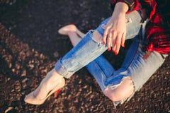 Девушка в сорванных джинсах сидя на дороге Стоковая Фотография