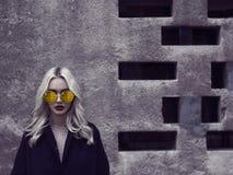 Девушка в солнечных очках идя в город Стоковая Фотография