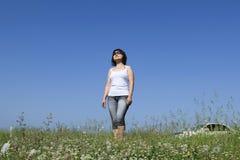 Девушка в солнечных очках стоит в поле цветка на летний день I стоковая фотография rf