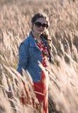 Девушка в солнечных очках стоя на поле в солнце излучает Стоковое Изображение