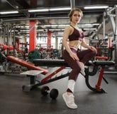 Девушка в спортзале с гантелью, в красивые спорт равномерные Стоковое Фото