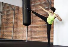 Девушка в спортзале ударяя грушу стоковое фото rf