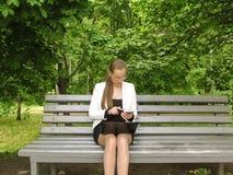 Девушка в стеклах набирает номер на экране смартфона сидя на стенде в парке Работа с технологией стоковое фото