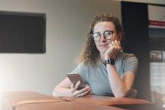 Девушка в стеклах одетых в striped футболке сидит на кресле, полагаясь ее голова на ее руке и смотря заботливо вне окно стоковые изображения