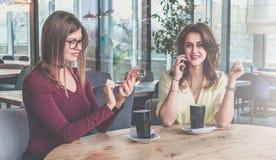 Девушка в стеклах использует smartphone, вторая девушка говорит сотовый телефон говорить встречи компьтер-книжки стола cmputer би Стоковые Изображения