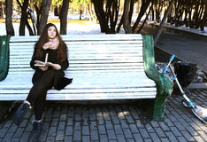 Девушка в стеклах с длинными волосами и книга сидят на стенде в парке Стоковые Изображения