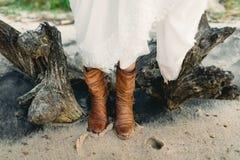 Девушка в стильных коричневых ботинках стоит на пляже рядом с пнем Изображение конца-вверх ног asama лестницы портрета платья при Стоковая Фотография