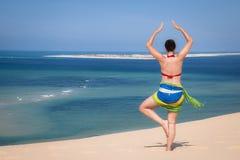 Девушка в стоящем представлении йоги в пляж Стоковая Фотография