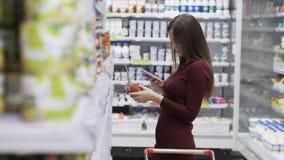 Девушка в супермаркете покупает еду, взглянет товары от полки и на телефоне видеоматериал