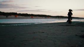 Девушка в темном платье бежать на пляже на заходе солнца Photoshoot ветер модель бобра сток-видео