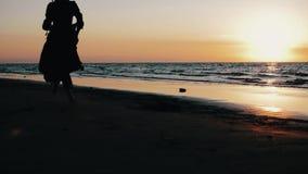 Девушка в темном платье бежать на пляже на заходе солнца Photoshoot Море модель бобра сток-видео