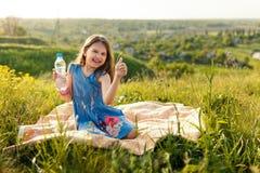 Девушка в траве с пластичной бутылкой с водой Стоковое Изображение