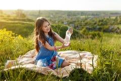 Девушка в траве с пластичной бутылкой с водой Стоковое фото RF