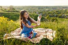Девушка в траве с пластичной бутылкой с водой Стоковая Фотография