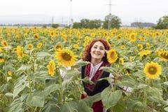 Девушка в традиционном болгарском платье в поле солнцецветов стоковое фото rf