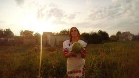 Девушка в традиционном костюме людей Urainian находит арбуз в саде и дает ее к персоне за камерой first акции видеоматериалы