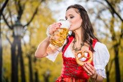 Девушка в традиционном баварском пиве Tracht выпивая из огромного mu стоковые фотографии rf