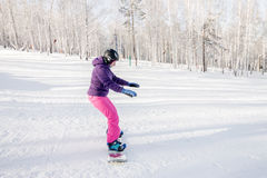Девушка в фиолетовой куртке и розовые брюки учат езду сноуборд Стоковая Фотография RF