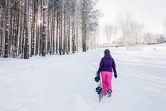 Девушка в фиолетовой куртке и розовых брюках с сноубордом в руках Стоковое Изображение RF