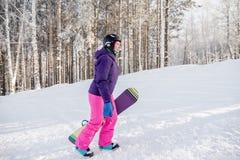 Девушка в фиолетовой куртке и розовых брюках с сноубордом в руках Стоковая Фотография