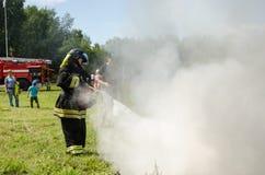 Девушка в форме пожарного тушит горящую автошину на тренировке стоковые фото