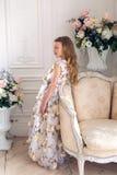 Девушка в флористическом платье сидя на поле Стоковые Изображения RF