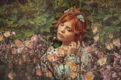 Девушка в цветках стоковая фотография rf