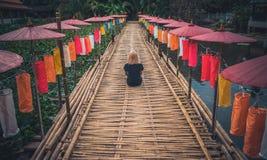 Девушка в черной футболке сидит с ей назад к камере на бамбуковом пути украшенном с яркими тайскими зонтиками стоковая фотография
