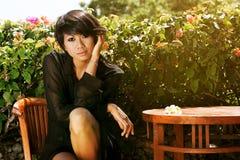 Девушка в черной шифоновой рубашке которая сидит на a стоковые изображения