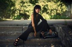 Девушка в черном костюме на лестницах обще брюнет Лето стоковое изображение